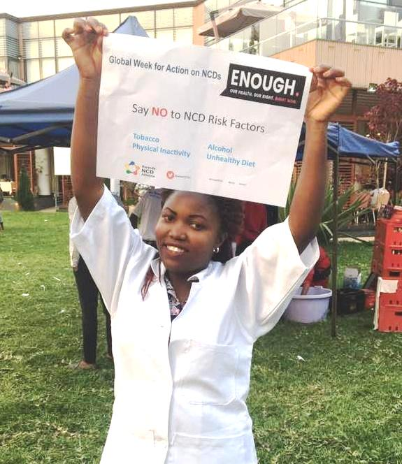 A member of Health Volunteers Initiative, Rwanda, holding up a sign celebrating the Global Week for Action on NCDs.