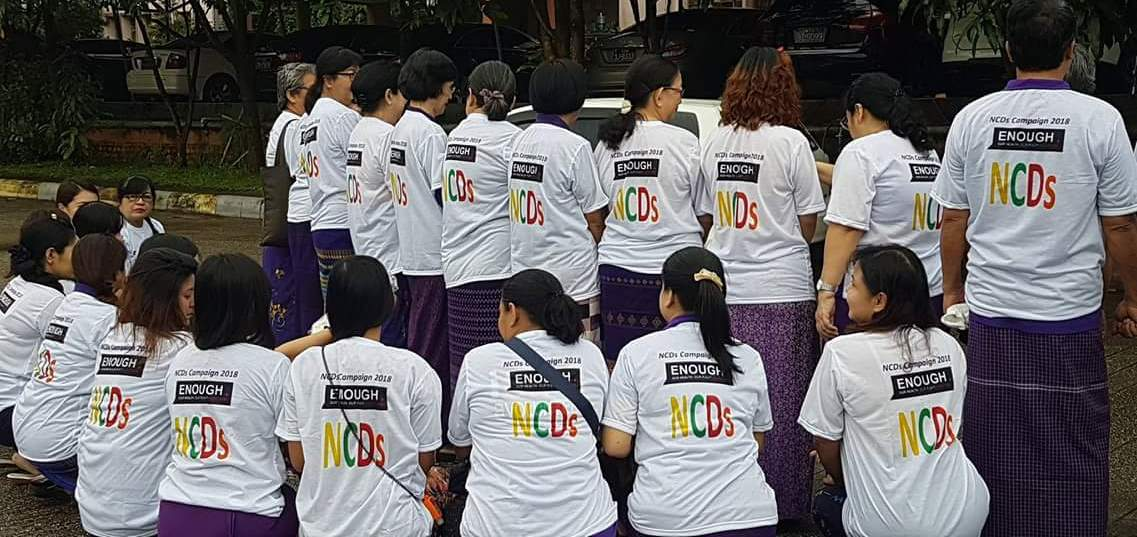 A dozen members of the Myanmar NCD Alliance wearing white T-shirts to mark the Global Week