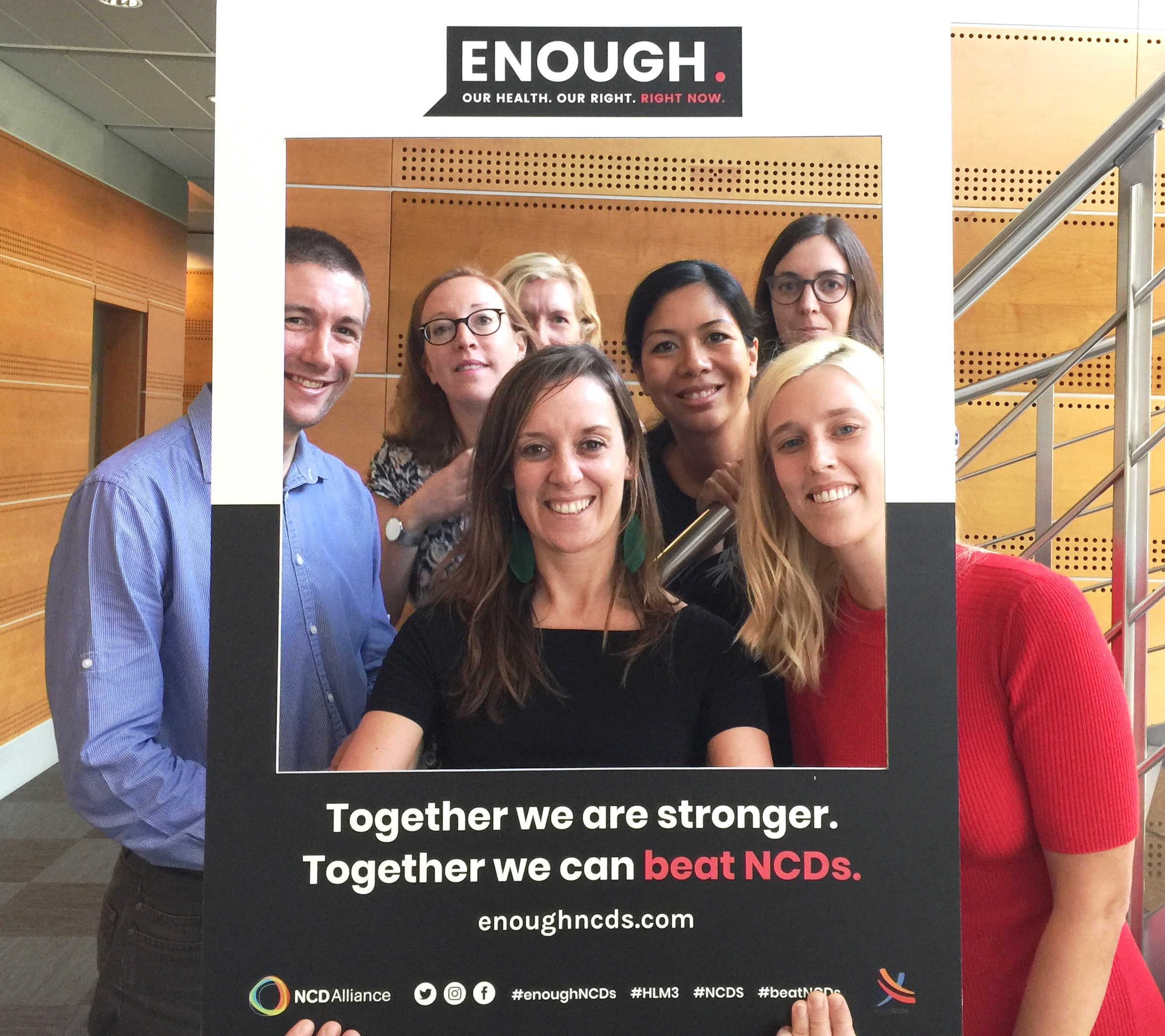 Staff from Union for International Cancer Control (UICC) appear in a giant frame, with branding of the ENOUGH NCDs campaign.