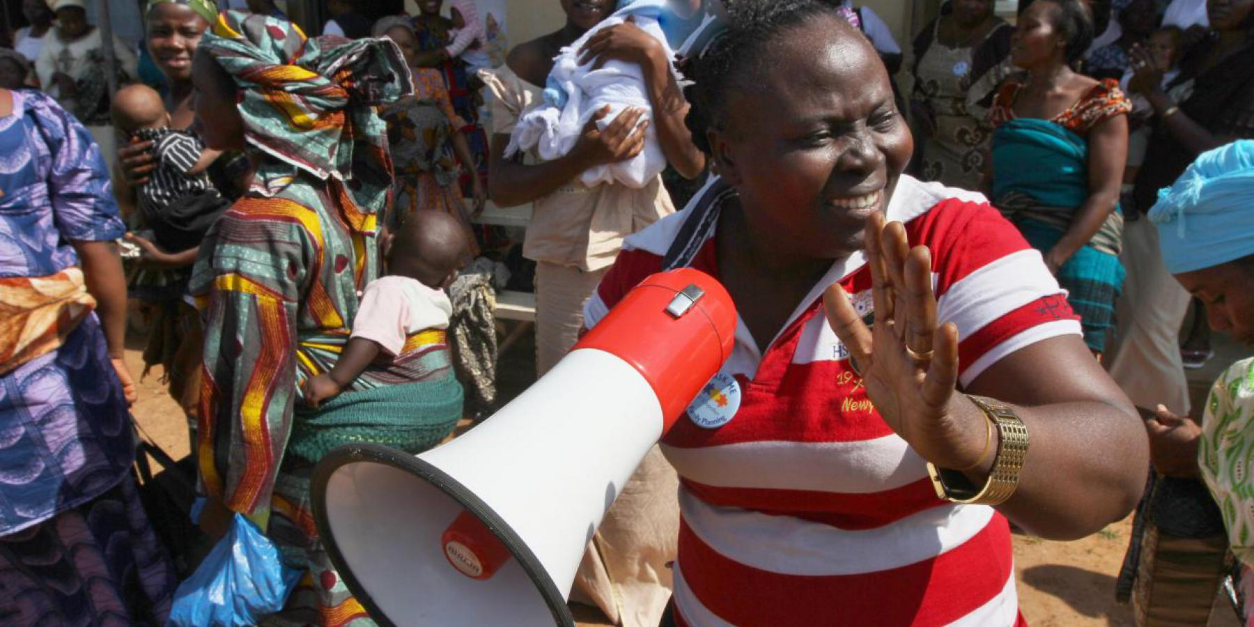 A family planning mobilizer sings with nursing mothers at the start of a family planning visibility parade in Omuaran township, Nigeria
