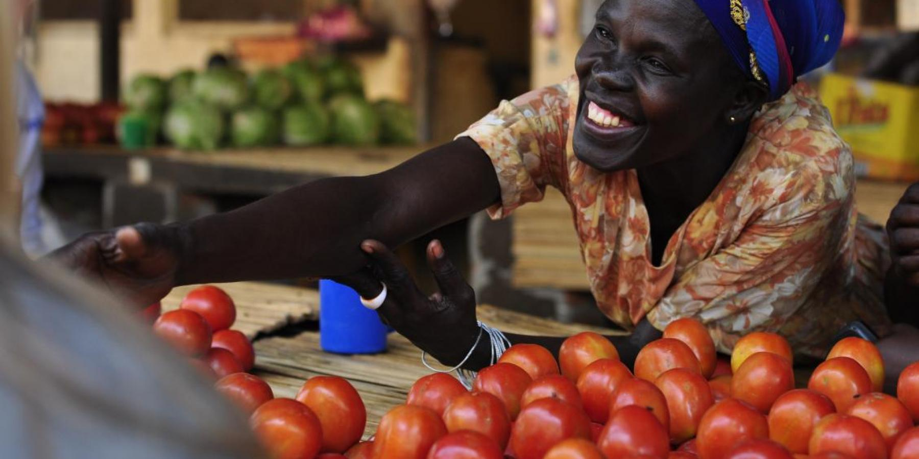 A member of a women's microfinance group sells produce at a market in Gulu, Uganda.