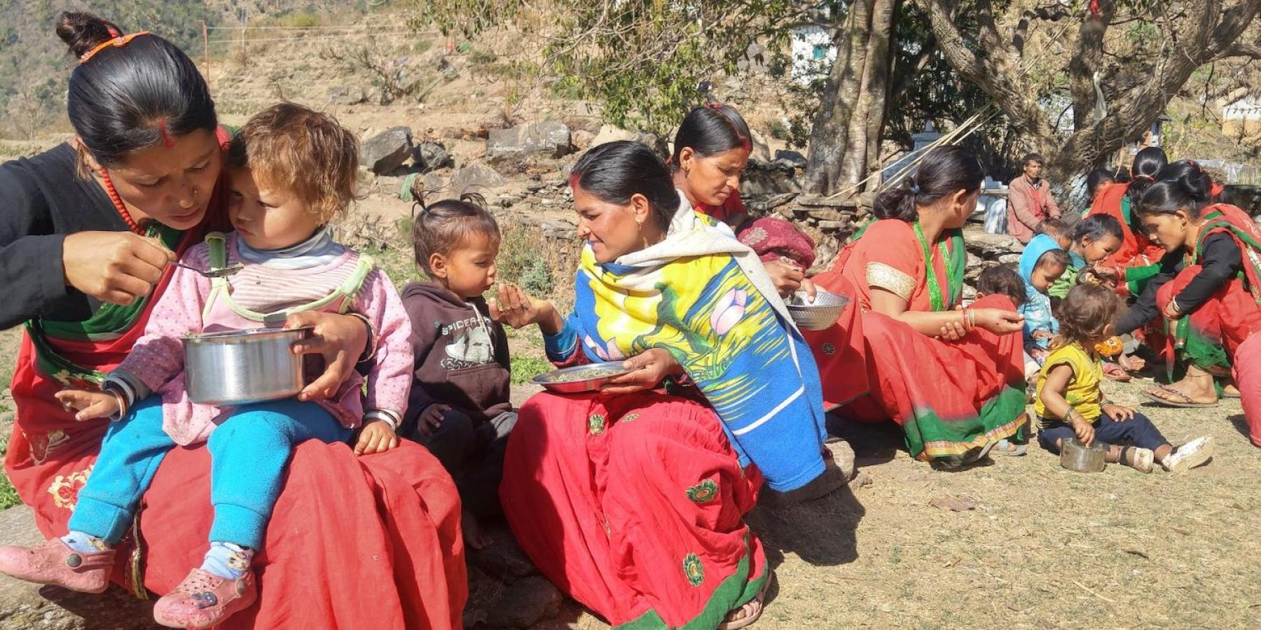 Women feed their children during a weekly mothers' group meeting in a village in Achham District, western Nepal, February 2018.