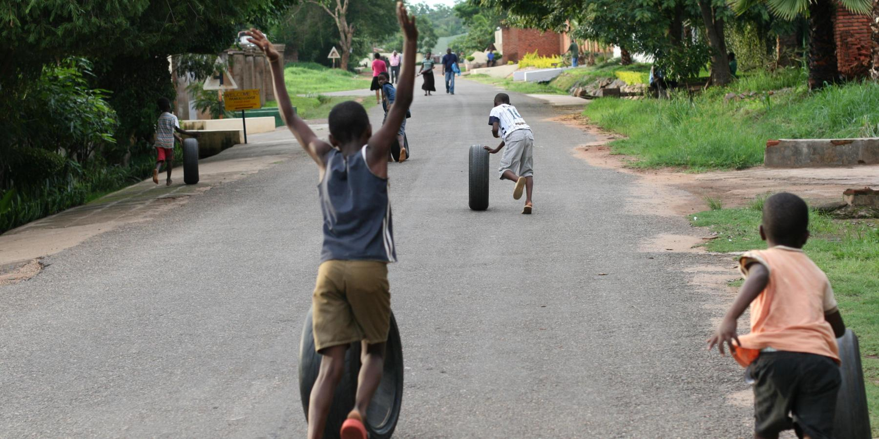 Children roll tires on a street in the Area 14 neighborhood of Lilongwe, Malawi