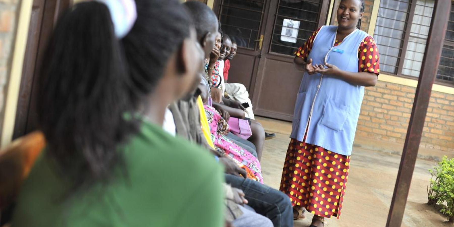 A health worker speaks to clients waiting for services at a clinic in Rwanda
