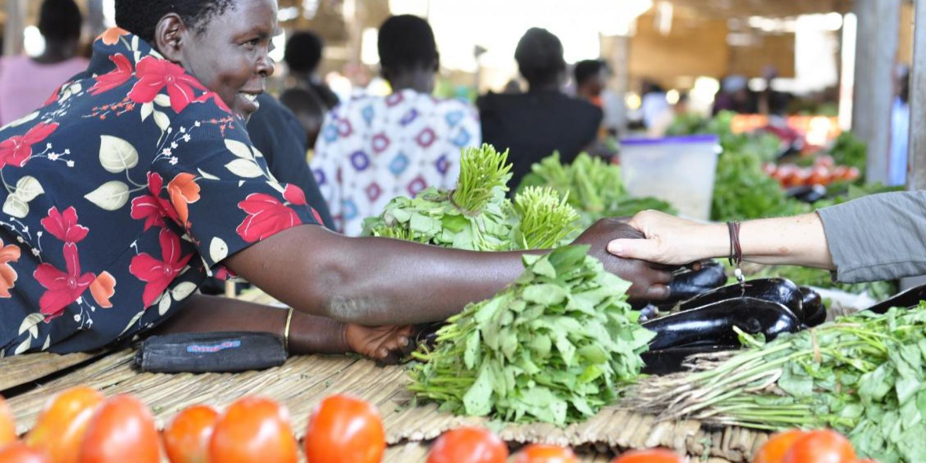 A member of a women's microfinance group sells fruits and vegetables in Gulu, Uganda.