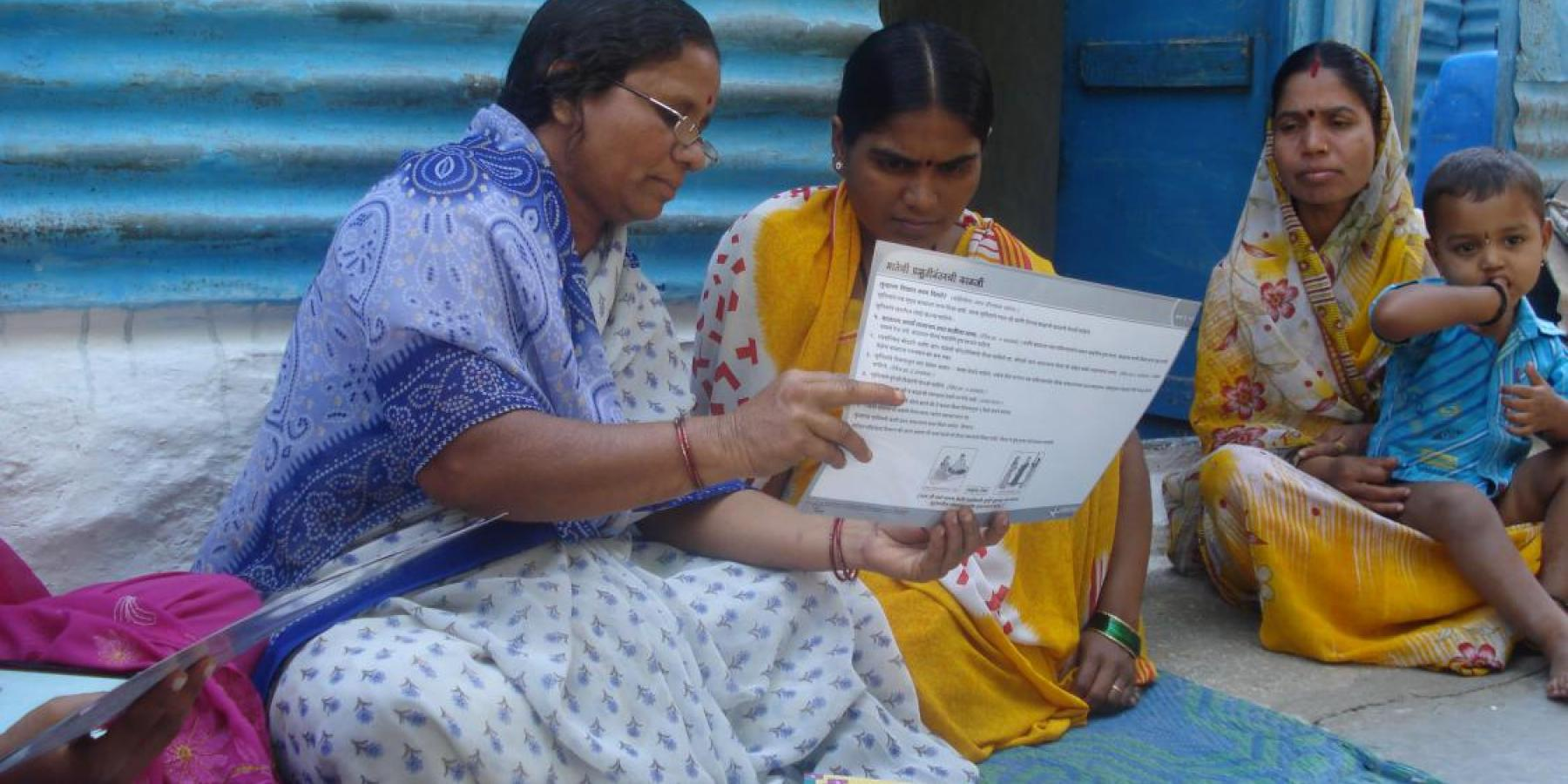 A self-help group (SHG) member provides a mother with information on infant and newborn care during a home visit in India.
