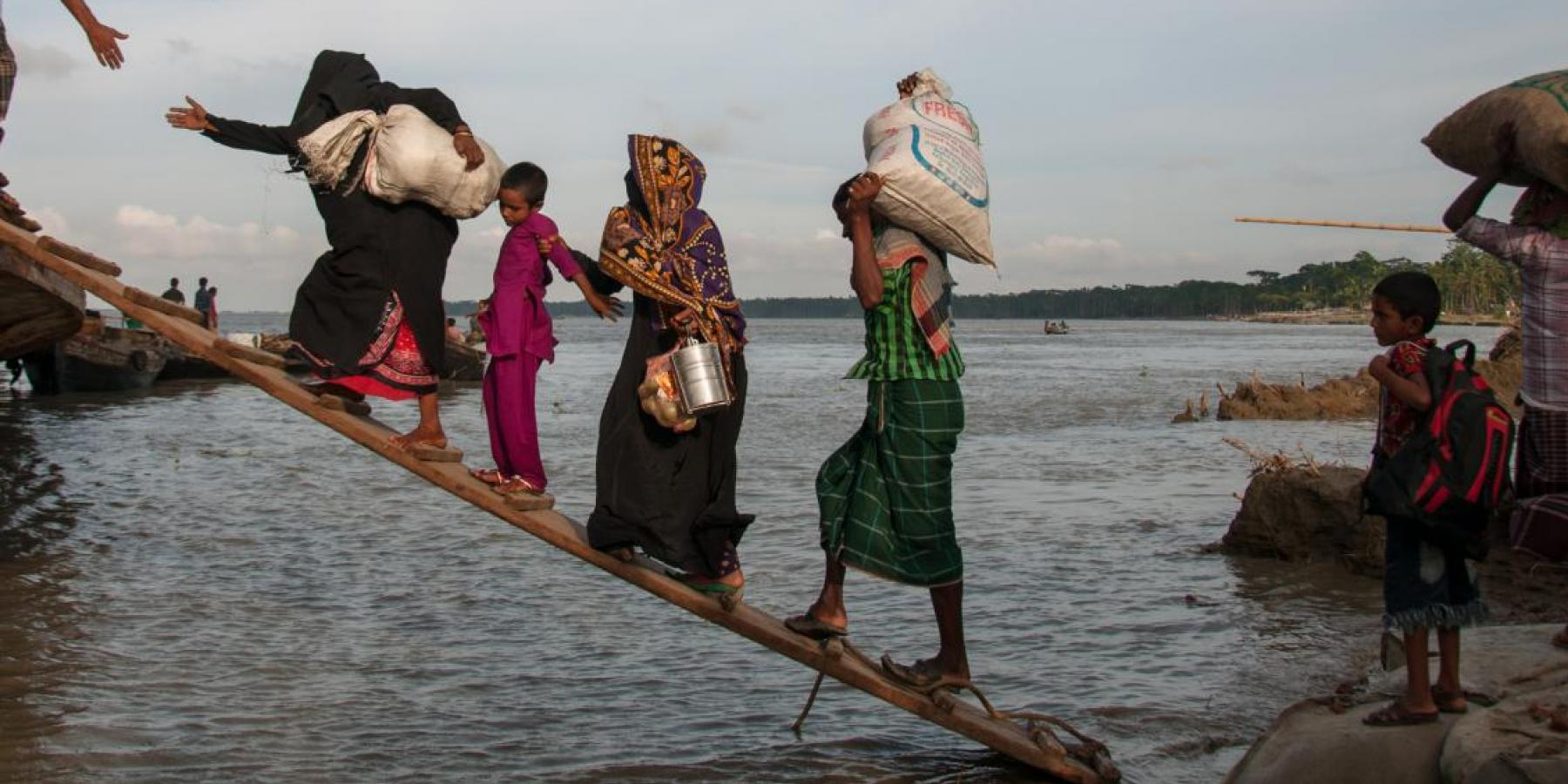 Climate-affected internally displaced persons board a boat to travel to Dhaka, Bangladesh.