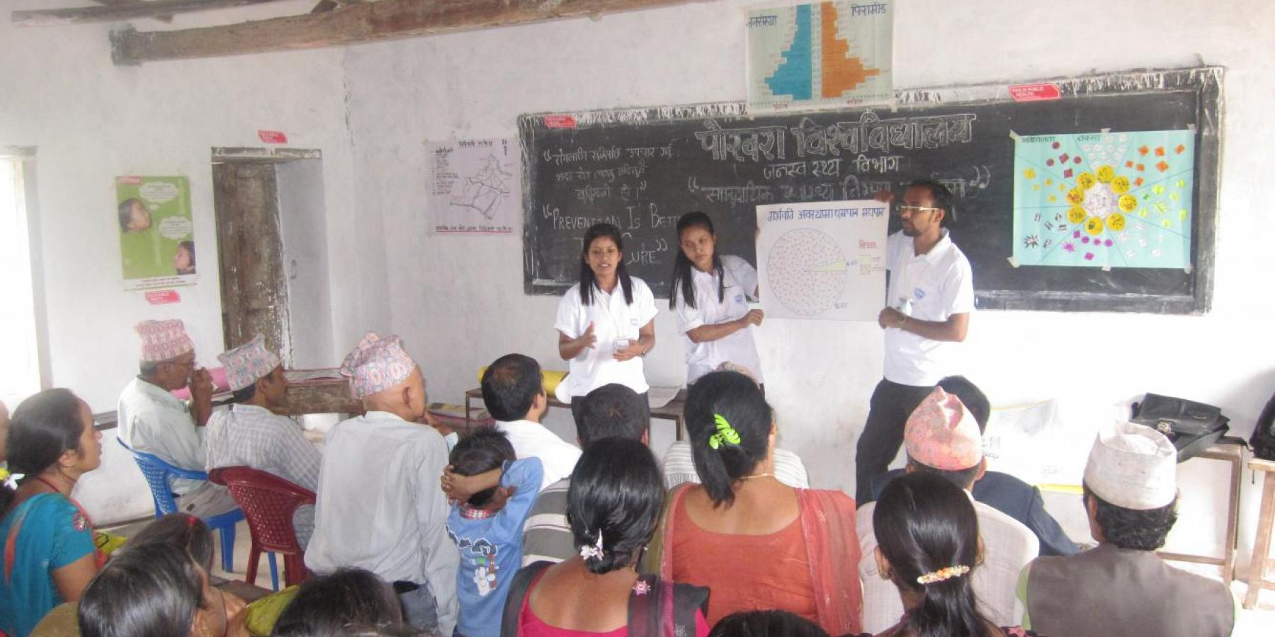 Health volunteers explain a pie chart with data on pregnant women's consumption of tobacco and alcohol to community members in Chidipani, Palpa, Nepal.