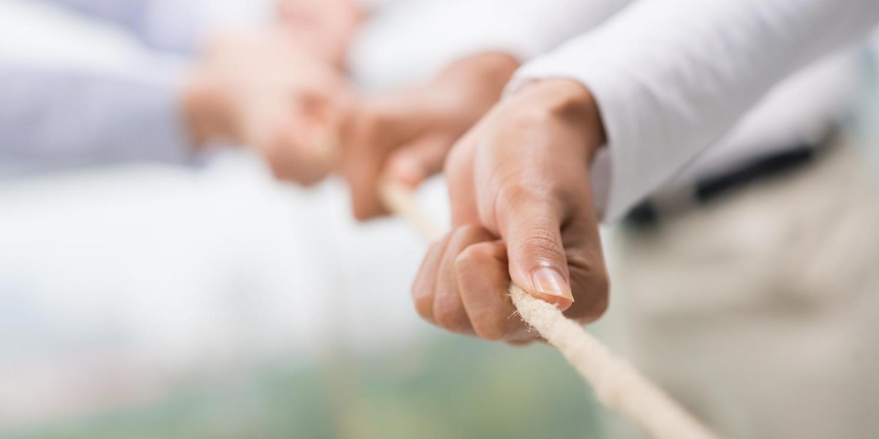 Close up of hands pulling a rope