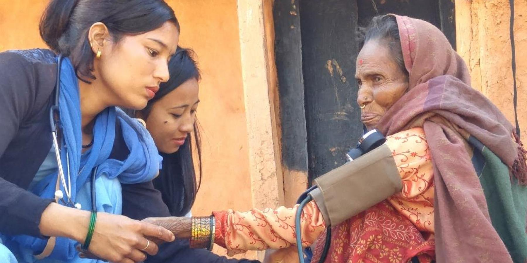 Community health workers check the blood pressure of a woman with breathing difficulties, Achham district, Nepal, Feb 2018