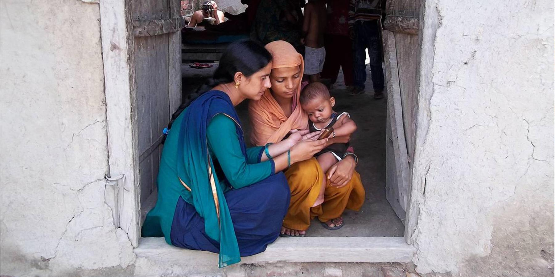 A community health worker uses mHealth to counsel a new mother in Badagaon, India