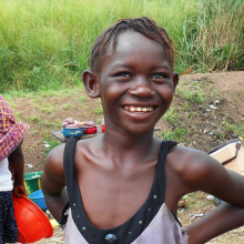 A girl smiles among vendors at a roadside Ebola check point in Port Loko Sierra Leone.