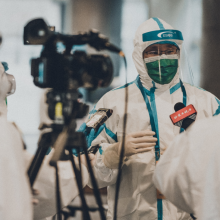 Men in white coat in media briefing. Photo by Unsplash