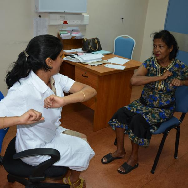 Diabetic Specialist Nurse in Port Louis, Mauritius, teaches a patient simple limb exercises