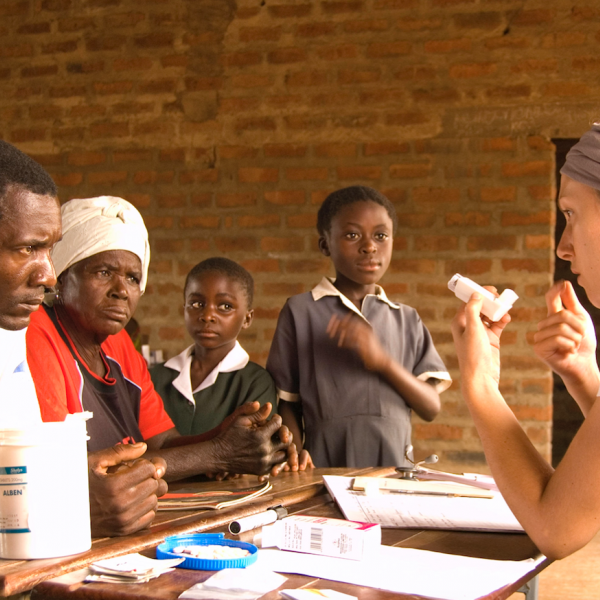 Family members in Mulindi village, Kazungula District, Zambia, listen as Dr. Mattea Clarke shows them how to manage their daughter's asthma