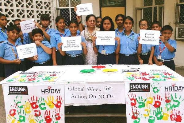 Members of HRIDAY in India, hold up small signs with slogans supporting the Week for Action.